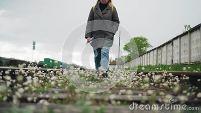 一个女孩沿着长满美丽花朵的铁轨走 美丽的风景 影视素材