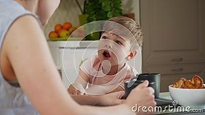 一个学前班男孩坐在厨房的桌子旁,与母亲交流 影视素材