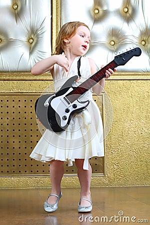 一个小女孩唱并且弹吉他图片