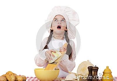 一个小女孩的画象一棵白色围裙和厨师帽子细片圆白菜的在厨房里,隔绝图片