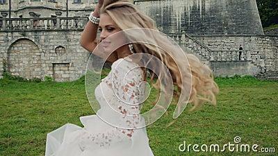 一个美丽的金发碧眼的女人的动态录影白色礼服的 影视素材
