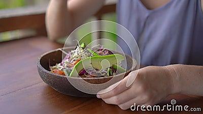 一位在热带咖啡馆吃健康素色拉的年轻女士 素食概念 慢镜头 影视素材