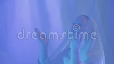 一位白衣的穆斯林年轻女子在婚礼前在白色幕布后做祷告 股票视频