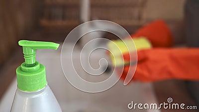 一只戴橙色手套的母手把清洁剂放在海绵上,擦洗厨房水槽上的盘子 — 这是家常便饭 影视素材