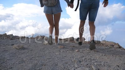 一对年轻的游客,背着背包,奔向美丽峡谷的边缘,并胜利地向上伸出双臂 股票录像