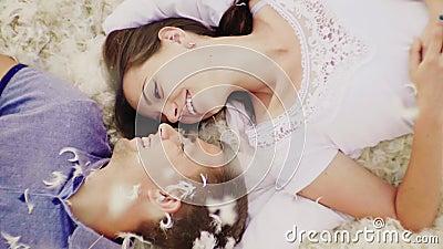 一对爱恋的夫妇在面对面的羽毛在 上面和下降羽毛和羽毛 慢动作录影 股票视频