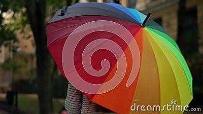 一把开放转动的五颜六色的彩虹伞的特写镜头视图在女性手上 慢动作射击 股票录像