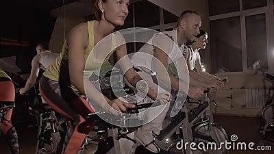 三训练在固定式自行车的运动的健身小组同步做锻炼