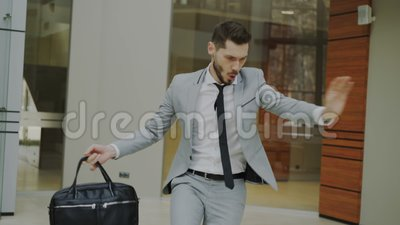 与公文包跳舞的愉快和滑稽的商人在办公室大厅,当观看他时的没人