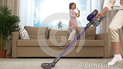 与吸尘器的主妇跳舞在客厅 她的跳跃在长沙发的小女儿 慢的行动 股票视频