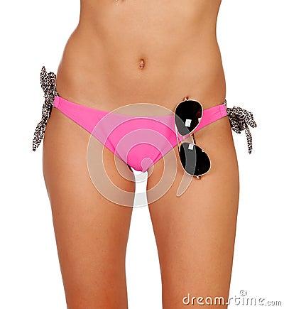 与桃红色游泳衣的有吸引力的身体和太阳镜