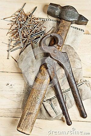与钉子的葡萄酒锤子在木背景