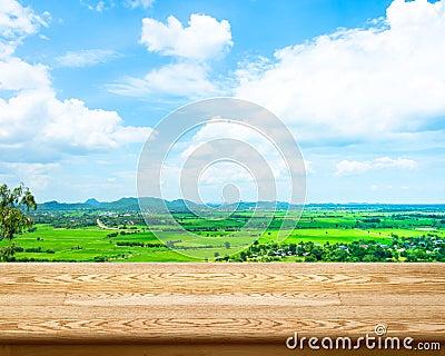天然和空哪个重_与绿色领域的空的木桌和在背景,显示产品的模板的蓝天.