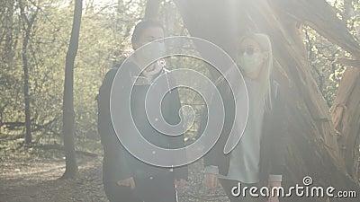两个女孩戴口罩在春雨林里散步离开的中拍 白种人女性在阳光明媚的日子 股票录像