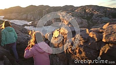 两个小女孩在岩石北海滨使用 影视素材