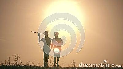 两个男孩使用与一架木飞机在日落 使用与飞机的孩子剪影  飞行梦想 作为背景诱饵概念美元灰色吊异常分支 影视素材