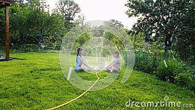 两女孩坐绿色草坪在运转的庭院喷水隆头附近 股票录像