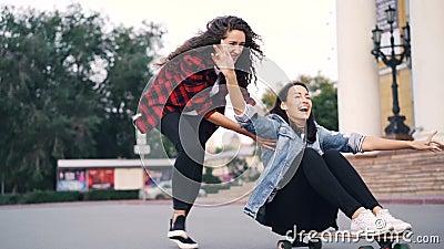 乘坐滑板的快乐的少妇朋友的慢动作坐它和推挤它在城市在夏日 影视素材
