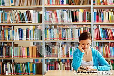 有开放书的读它的聪明的学生画象在大学图书馆里.