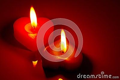 在一张红色表的二个燃烧的心形的蜡烛.图片