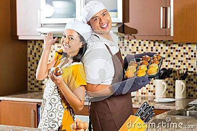 亚洲夫妇烘烤松饼在家庭厨房里