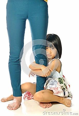 亚洲小女孩拥抱妇女的腿的和哀伤