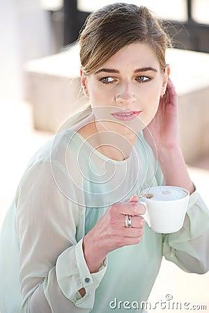 享用一杯咖啡的美丽的妇女户外