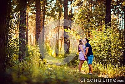 亲吻在背景夏天森林的浪漫年轻夫妇.图片