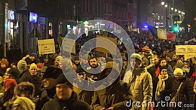 人们走在晚上街道上的,与招贴的人群