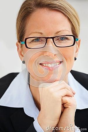 佩带妇女的微笑的眼镜