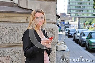使用一个巧妙的电话的一个愉快的年轻女商人户外