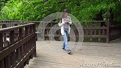 使用在木桥的少年女孩手机 在智能手机走的青少年短信的消息 行动照相机 股票视频