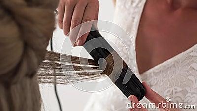使用头发铁的发式专家为卷曲的一会儿发型对年轻女人在秀丽演播室 关闭 美发师做 影视素材