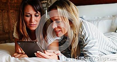 使用数字片剂的女同性恋的夫妇在床4k上 股票视频