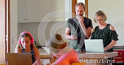 使用膝上型计算机和手机的父母,当学习的孩子在厨房4k时 股票录像