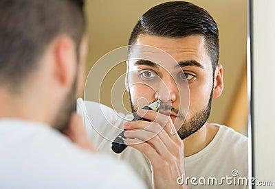 使用整理者的人为取消头发在他的在镜子前面的鼻子.图片