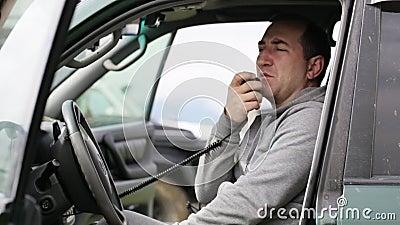 供以人员拿着手microphon和谈话在他的汽车的收音机 影视素材