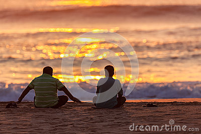供以座位的日出两亚洲男性海滩 图库摄影片