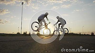 做上流五的青少年的骑自行车的人夫妇,当执行在他们的自行车的一个惊人的前面自行车前轮离地平衡特技-时 股票录像