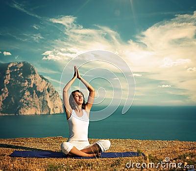做瑜伽的婦女在海和山 庫存圖片圖片