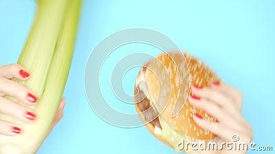 健康和不健康的食物的概念 反对汉堡包的芹菜茎在明亮的蓝色背景 女性手与 影视素材