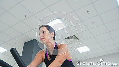 健身室自行车课上室内自行车的微笑女子训练 健身训练低角度快乐女子自行车 影视素材