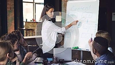 公司教练员解释新的信息对人,站立在whiteboard,谈话并且指向在 股票视频