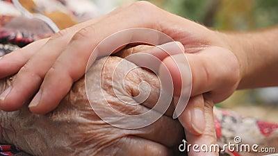 关闭年轻男性手安慰室外老妇人的年长的胳膊 孙子和祖母消费时间 股票视频