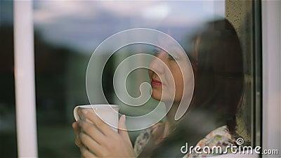关闭 体贴的哀伤的深色的妇女外部饮用的温暖的早晨茶和Â作梦 股票录像