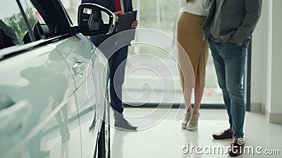 兴旺的人民年轻夫妇低射击在经销权中买新的汽车和谈话与衣服的有用的经理 发光 股票录像