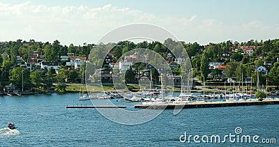 利丁戈,瑞典 夏日阳光明媚时,游船在港边漂浮 股票录像