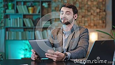 办公室里,面带微笑、帅气的经理直视着他坐在办公地点的相机,拿起数字平板电脑 影视素材