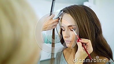 化妆师和发式专家式样妇女为时装慢动作做准备 股票视频