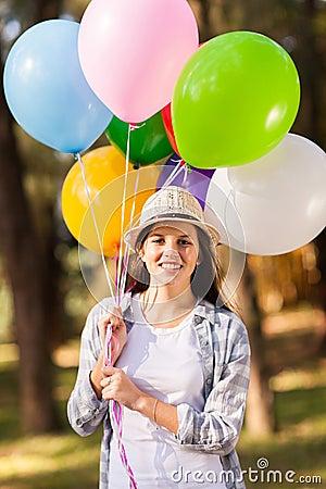 几岁_拿着束氦气的美丽的十几岁的女孩迅速增加户外.